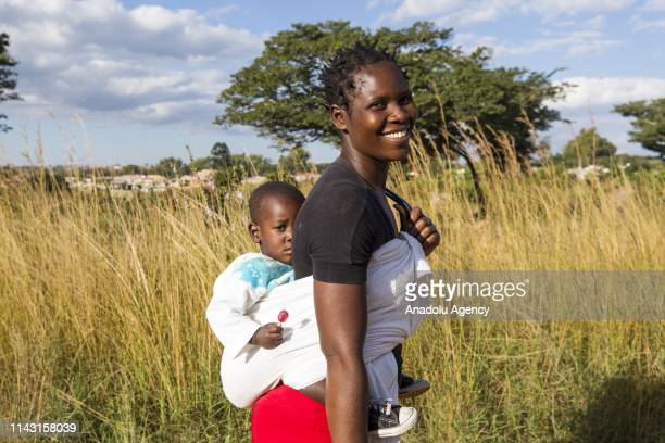 Zimbabwean mother poses for a photo with her baby on her back during their daily lives in Harare Zimbabwe on May 11 2019