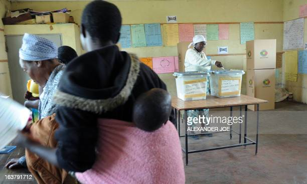 Zimbabwean mothers with children stand in line waiting to cast their vote in Epwath on March 16 2013 for Zimbabwe's referendum for a new constitution...