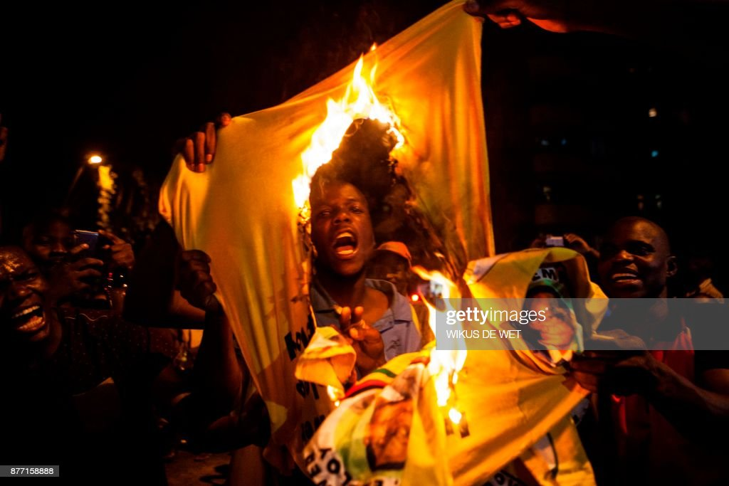 Zimbabwean national burns a shirt of the Zimbabwe's ruling party, the Zimbabwe African National Union Patriotic Front (ZANU PF), as hundreds of Zimbabweans living in South Africa celebrate the resignation of Zimbabwe's president Robert Mugabe in the streets of the district of Hillbrow in Johannesburg on November 21, 2017. The announcement came after days of mounting pressure on the 93-year-old leader, whose long and authoritarian rule made him feared by many of his citizens. /