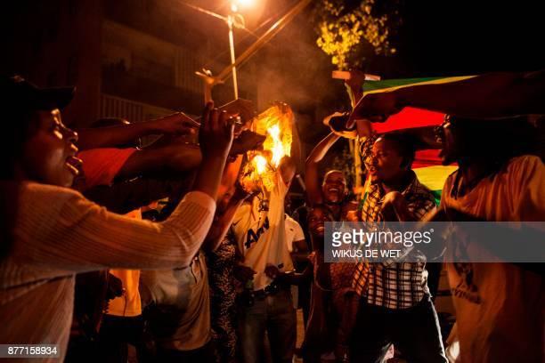 Zimbabwean nationals burn a shirt of the Zimbabwe's ruling party the Zimbabwe African National Union Patriotic Front as hundreds of Zimbabweans...