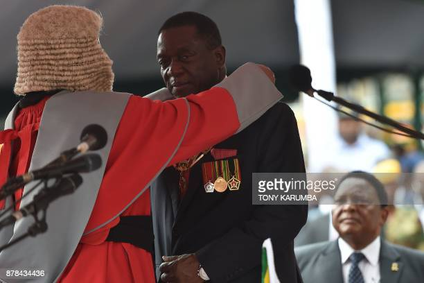 Zimbabwean new interim President Emmerson Mnangagwa receives the chain and sash of office from the Chief judge of the Supreme Court Chief Justice...