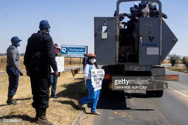 Zimbabwean novelist Tsitsi Dangarembga and a colleague Julie Barnes hold placards as they are arrested during an anticorruption protest march along...