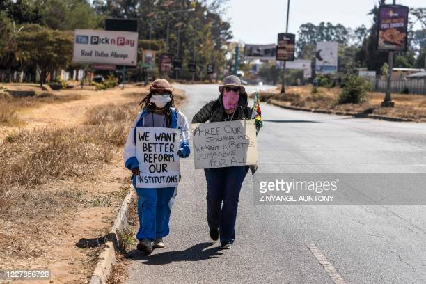 TOPSHOT Zimbabwean novelist Tsitsi Dangarembga and a colleague Julie Barnes hold placards during an anticorruption protest march along Borrowdale...