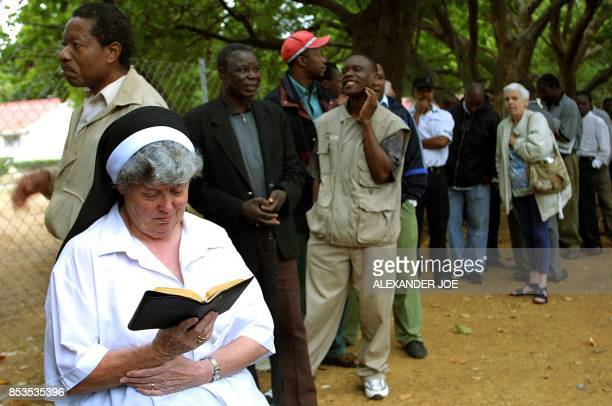 A Zimbabwean nun prays at the head of a line as others wait 09 March 2002 to vote at a polling station in Harare at the start of two days of voting...