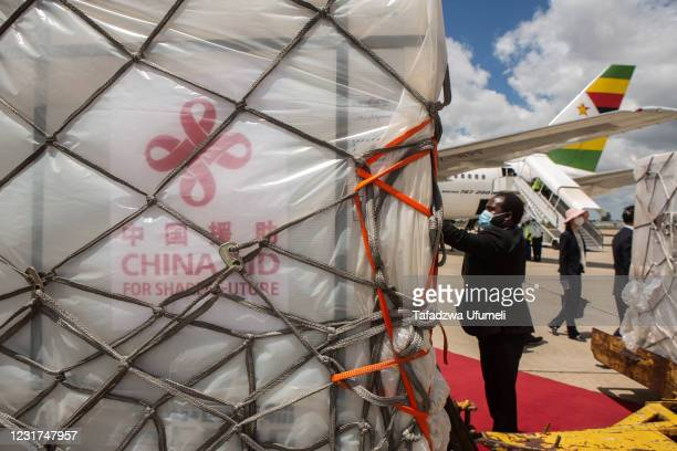Zimbabwean officials inspects the shipment of the Sinovac and Sinopharm vaccines at Harare International Airport on March 16, 2021 in Harare,...