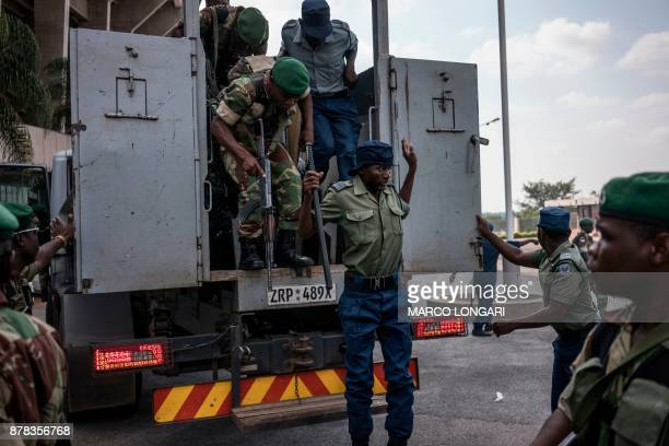 A Zimbabwean policeman motions as he alight from an armored vehicle at the National Sport Stadium in Harare on November 24 2017 ahead of the newly...
