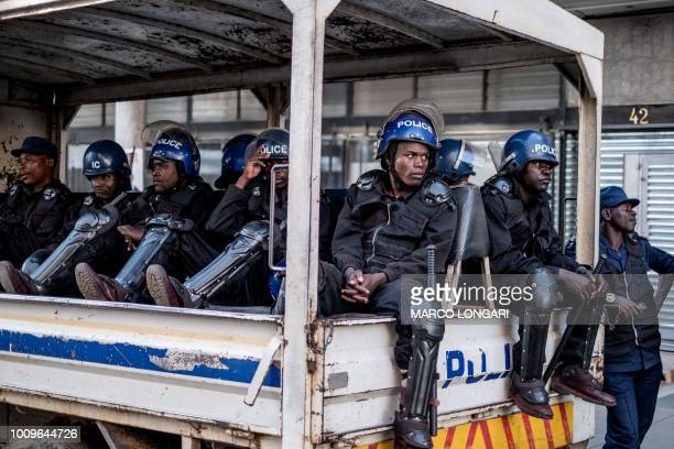 TOPSHOT Zimbabwean policemen sit in a vehicle stationed outside the headquarters party Movement for Democratic Change Alliance in Harare on August 2...