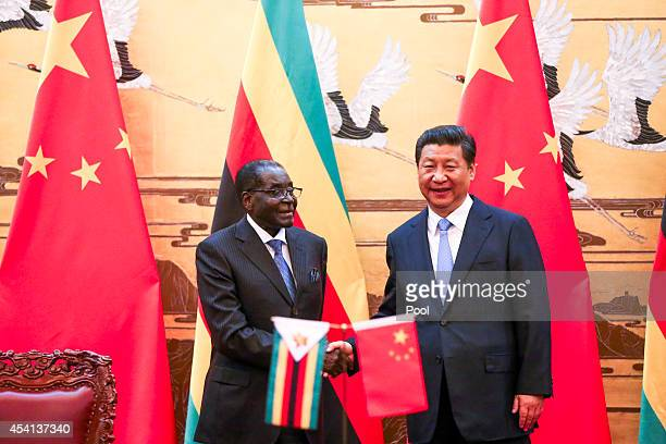 Zimbabwean President Robert Mugabe and his Chinese counterpart Xi Jinping participate in a signing ceremony at the Great Hall of the People on August...