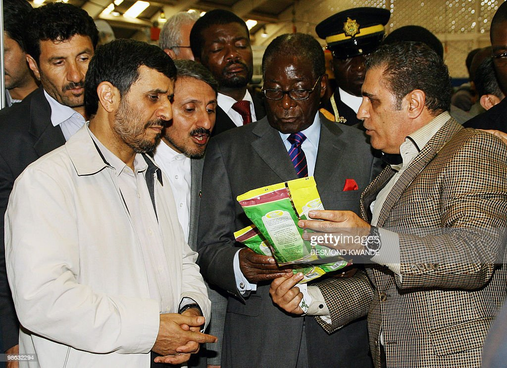 Zimbabwean President Robert Mugabe (C) and Iran's President Mahmoud Ahmadinejad (L) look at a product manufactured by Iranian businessman Kahali Ahmad (R) during the Bulawayo international trade fair on April 23, 2010, in Zimbabwe's second city of Bulawayo. Iran's President Mahmoud Ahmadinejad accused world powers of trying to destroy the economies of Zimbabwe and his own nation, which faces the threat of toughened sanctions. AFP PHOTO/Desmond Kwande