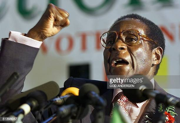 Zimbabwean President Robert Mugabe clenches his fist to salute Zanu PF comrades in Harare 03 May 2000 Mugabe launched his ruling party election...