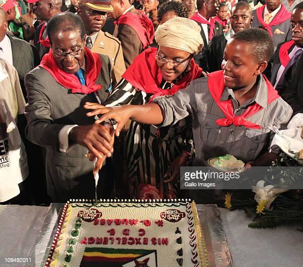 Zimbabwean President Robert Mugabe cuts his birthday cake with his wife Grace Mugabe and son Bellarmine Chatunga Mugabe during celebrations for his...