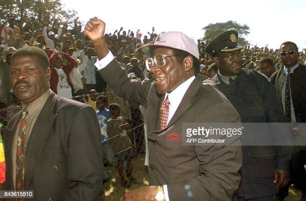 Zimbabwean president Robert Mugabe greets supporters at a rally in Chinhoyi 23 June on the eve of the parliamentary elections Mugage is facing a...