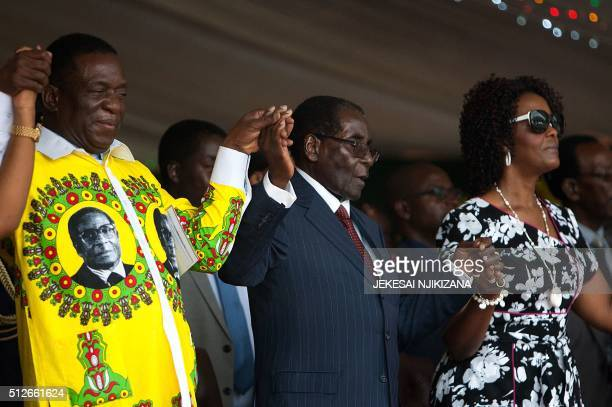 Zimbabwean President Robert Mugabe holds hands with Vice President Emmerson Mnangagwa and First Lady Grace Mugabe during celebrations marking his...
