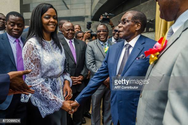 Zimbabwean President Robert Mugabe is congratulated by First Lady Grace Mugabe after he unveiled a plaque at the country's main international airport...