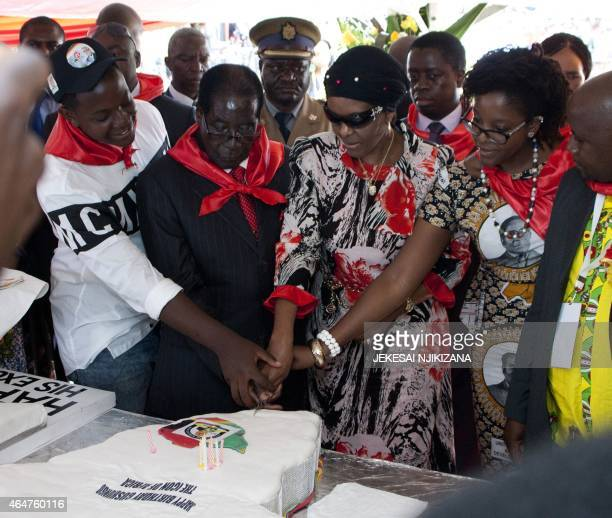 Zimbabwean President Robert Mugabe lady Grace Mugabe and his daughter Bona cut a birthday cake on February 28 2015 during the celebration of Mugabe's...