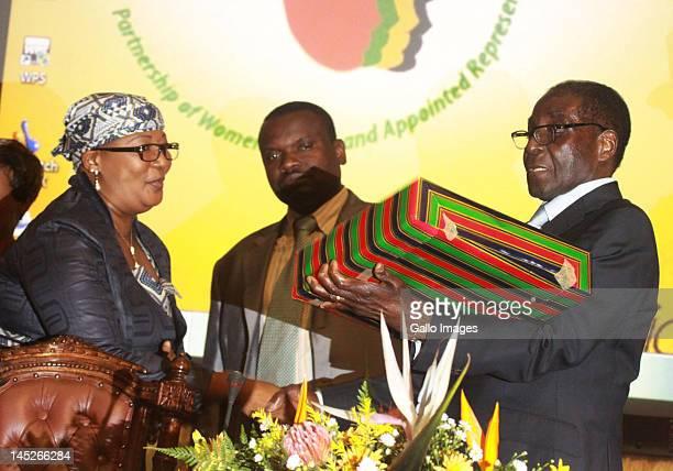Zimbabwean President Robert Mugabe receives a token of appreciation from Thokozani Khupe, President of Global Power Women Network and deputy Prime...