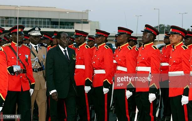 Zimbabwean President Robert Mugabe walks past a guard of honour as he arrives at the Kamuzu International Airport in Lilongwe on August 16 ahead of...