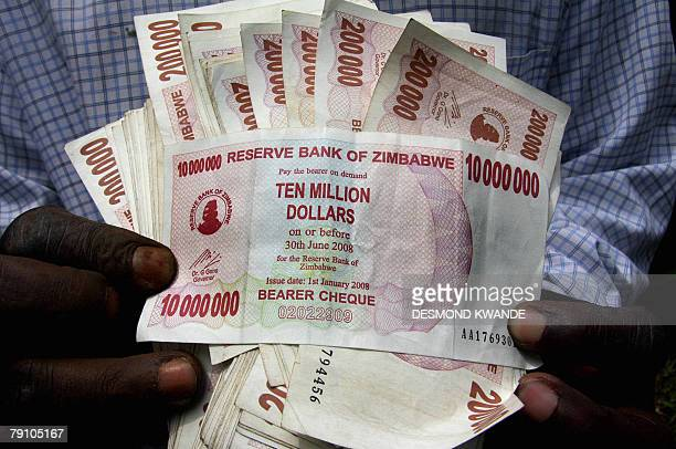 A Zimbabwean shows off the new $10000000 note after withdrawing cash form a local bank 18 January 2008 in HarareThe reserve bank of Zimbabwe...