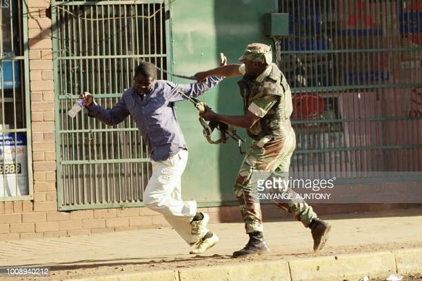 Zimbabwean soldier beats a man in a street of Harare on August 1 2018 as protests erupted over alleged fraud in the country's election One man was...