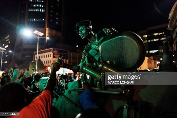 Zimbabwean soldier sitting in tank gestures as people greet and celebrate after the resignation of President Mugabe in Harare on November 21 2017...