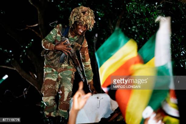 Zimbabwean soldier smiles as he stands next to Zimbabweans celebrating in the street of Harare after the resignation of President Mugabe on November...