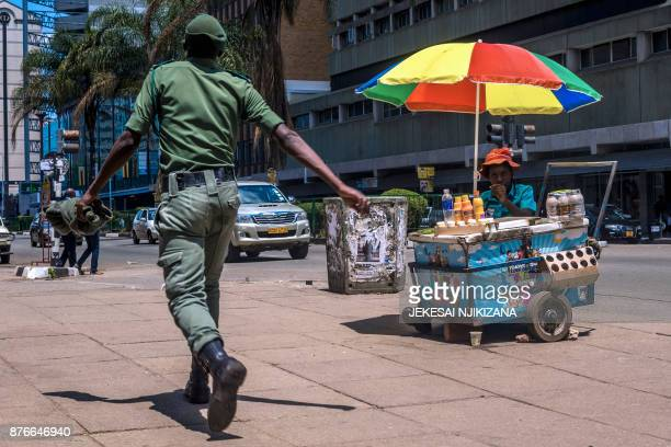 A Zimbabwean soldier walks by a street vendor in Harare's Central Business District main streets on November 20 2017 Zimbabwe is locked in one of its...