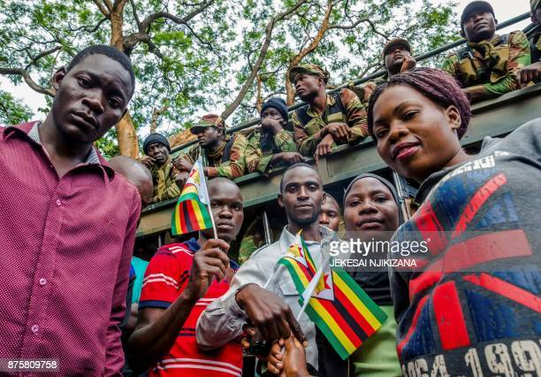 Zimbabwean soldiers block the way to people who demonstrate to demand the resignation of Zimbabwe's president near the State House on November 18...
