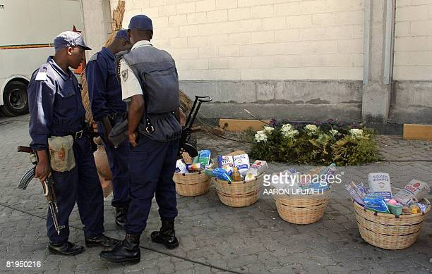 Zimbabwean soldiers look at food baskets a few moments before the arrival of Zimbabwean President Robert Mugabe for the opening of the 'People's...