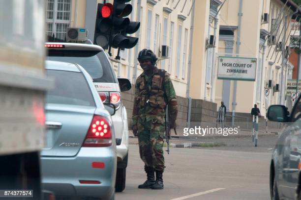 Zimbabwean soldiers stand by an intersection as they regulate civilian traffic in front of the High Court of Zimbabwe in Harare on November 15 2017...