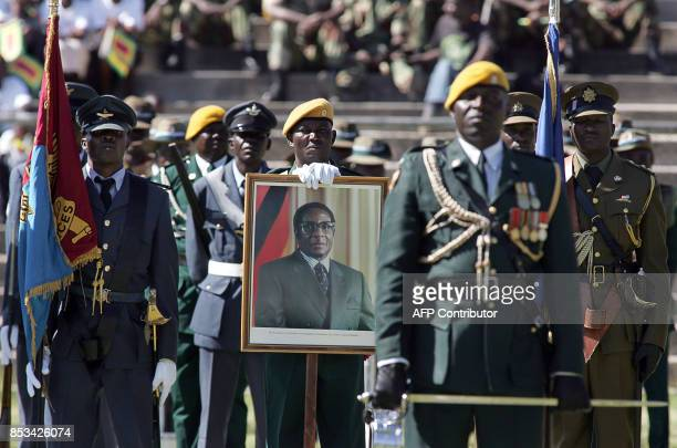 Zimbabwean troops holding a portrait of President Robert Mugabe parade in Harare on April 18 2008 during celebrations marking the country's 28th...
