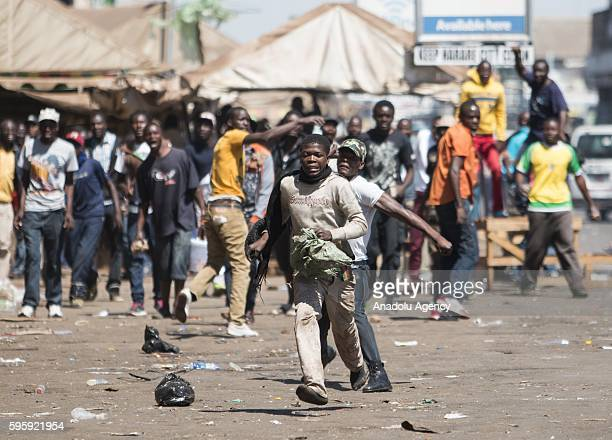 Zimbabweans clash with security forces during a protest against President of Zimbabwe Robert Mugabe and his government in Harare Zimbabwe on August...