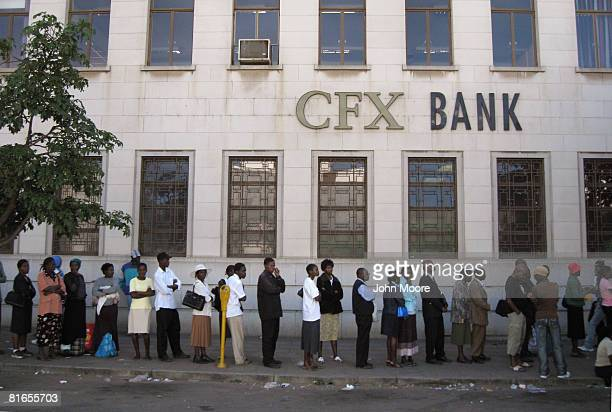 Zimbabweans queue to withdraw money from a bank June 21 2008 in Bulawayo Zimbabwe Because of hyperinflation and the lack of newly printed...