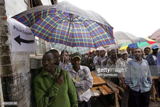 Zimbabweans wait in line and under the rain outside a polling station to cast their vote in the country's parliamentary election 31 March 2005 in...