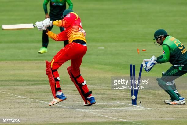 Zimbabwe's batsman Blessing Muzarabani is bowled as Pakistan's wicketkeeper Sarfraz Ahmed looks on during the first one day international cricket...