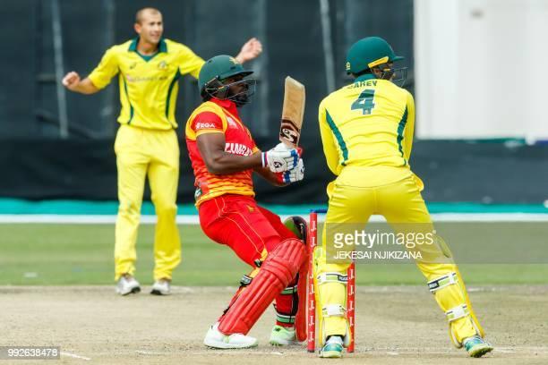 Zimbabwe's batsman Solomon Mire plays a shot past Australian wicketkeeper Alex Carey during the sixth T20 cricket match between Australia and host...