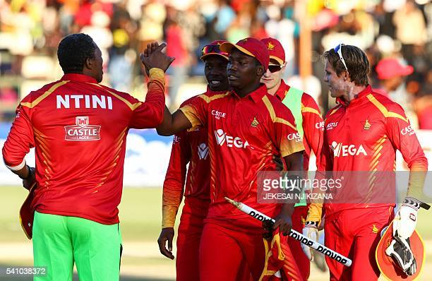 Zimbabwe's bowler Neville Madziva shakes hands with team coach Makhaya Ntini after victory during the first T20 cricket match in a series of three...