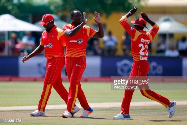 Zimbabwe's Brandon Mavuta celebrates after fielder Elton Chigumbura and bowler Tendai Chatara dismissed South Africa's Aiden Markram during the first...