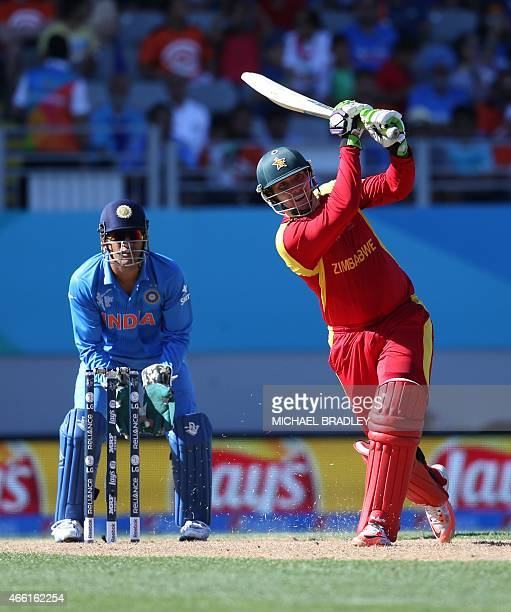 Zimbabwe's Brendan Taylor plays a shot watched on by India's Mahendra Singh Dhoni during the Pool B Cricket World Cup match between India and...