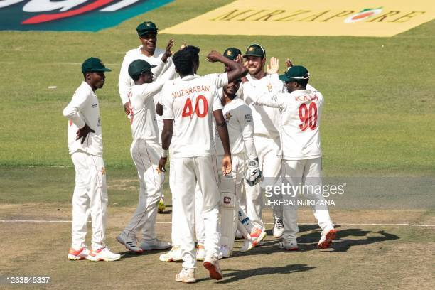 Zimbabwe's captain Brendan Taylor celebrates with teammates after taking a wicket during the first day of the Test cricket match between Zimbabwe and...