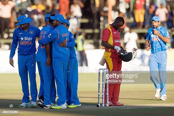 Zimbabwe's captain Elton Chigumbura reacts as India's players celebrate at the end of the first game in a series of 3 ODI cricket matches between...
