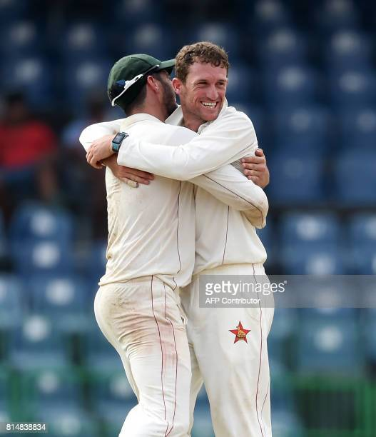 Zimbabwe's captain Graeme Cremer and Sean Williams celebrate after dismissing Sri Lankan cricketer Angelo Mathews during the Second day of the only...