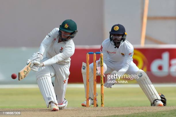 Zimbabwe's captain Sean Williams plays a shot as Sri Lanka's Niroshan Dickwella looks on during the first day of the second Test cricket match...
