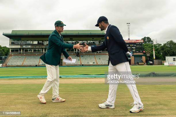 Zimbabwe's captain Sean Williams shakes hands with Sri Lanka's captain Dimuth Karunaratne ahead of the first day of the first Test cricket match...