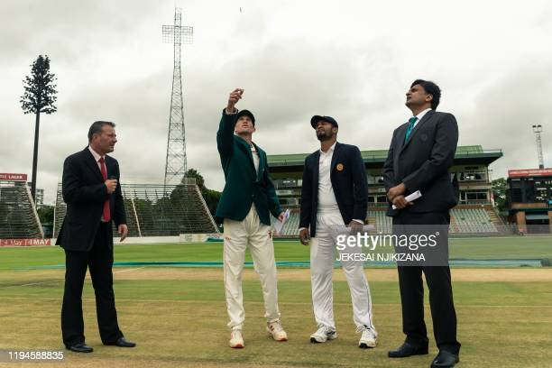 Zimbabwe's captain Sean Williams tosses the coin with Sri Lanka's captain Dimuth Karunaratne ahead of the first day of the first Test cricket match...