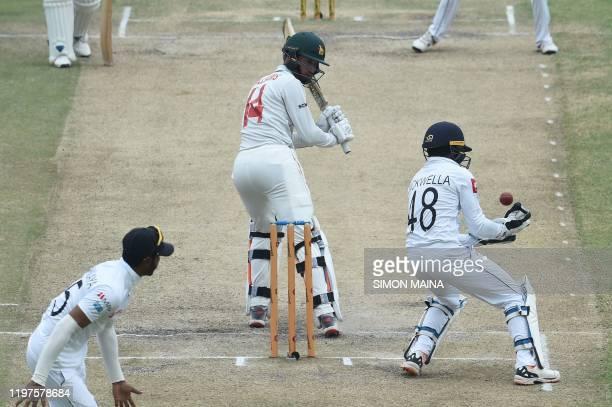Zimbabwe's captain Sean Williams watches the ball while Sri Lanka's Niroshan Dickwella tries to catch the ball as Sri Lanka's Lasith Embuldeniya...