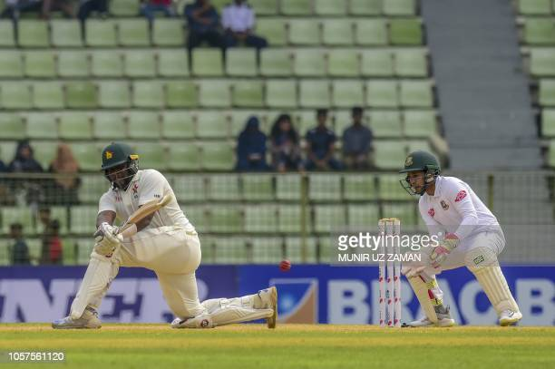 Zimbabwe's cricket captain Hamilton Masakadza plays a shot as Bangladeshi cricketer Mushfiqur Rahim looks on during the third day of the first Test...