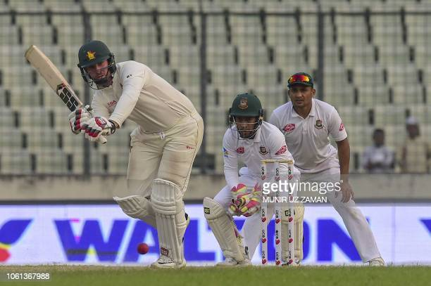 Zimbabwe's cricketer Brendan Taylor plays a shot as the Bangladeshi cricketers Mushfiqur Rahim and Ariful Haque look on during the fourth day of the...