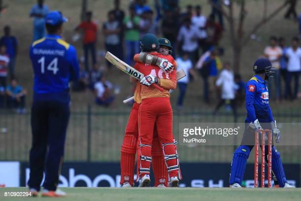 Zimbabwe's cricketer Craig Ervine hugs his teammate Peter Moor soon after scoring the winning runs during 4th oneday international cricket match...