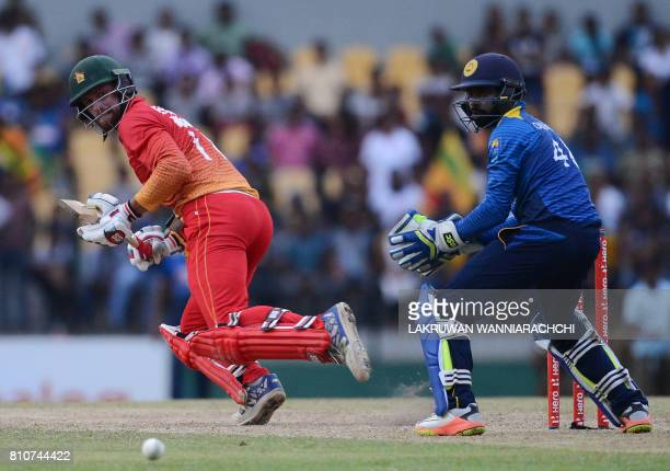 Zimbabwe's cricketer Craig Ervine is watched by Sri Lankan wicketkeeper Niroshan Dikwella as he plays a shot during the fourth oneday international...
