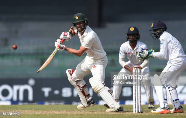 Zimbabwe's cricketer Craig Ervine plays a shot as Sri Lankan wicketkeeper Niroshan Dickwella looks on during the first day of the only oneoff Test...